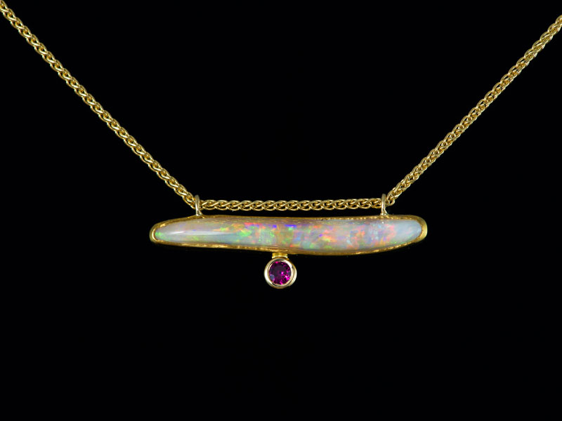 White Australian opal and ruby set in fine yellow gold